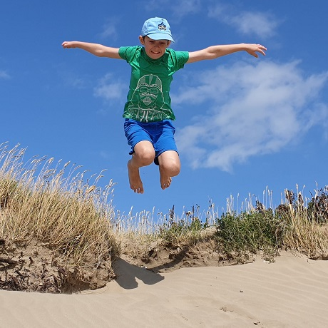 Young boy jumping in a dune